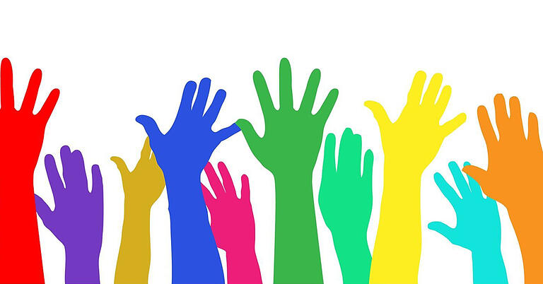 diverse colors of hands raised