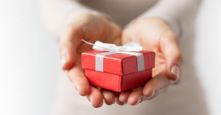 hands holding red gift box holiday giving