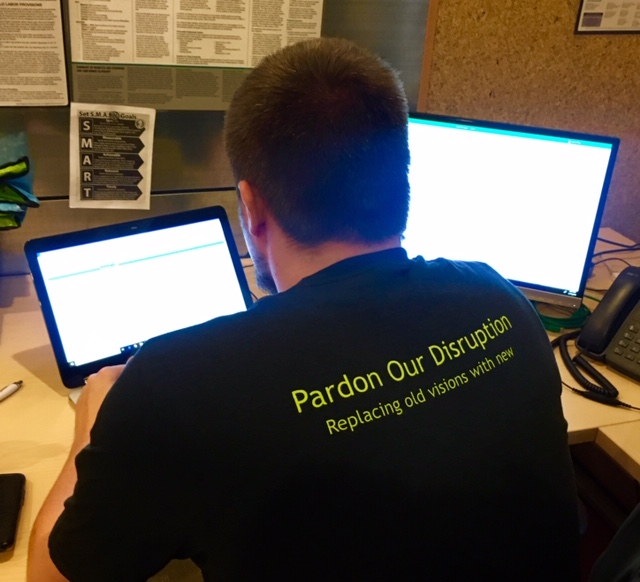 Daxtra employee working with computer monitors in background